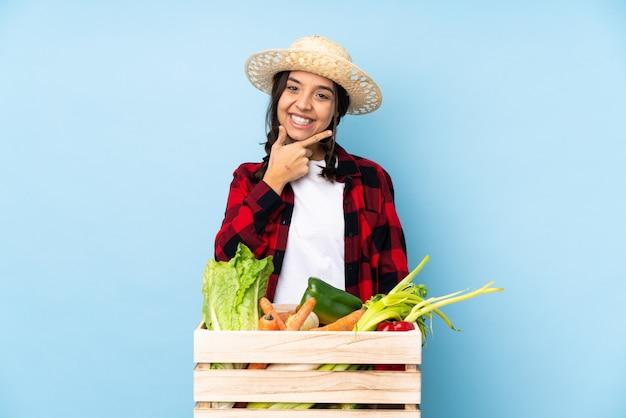 Jeune agriculteur femme tenant des légumes frais dans un panier en bois souriant