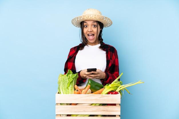 Jeune agriculteur femme tenant des légumes frais dans un panier en bois surpris et en envoyant un message