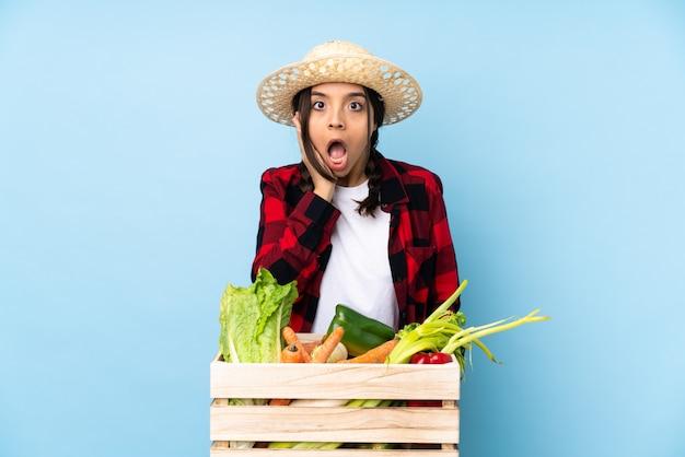 Jeune agriculteur femme tenant des légumes frais dans un panier en bois avec surprise et expression faciale choquée
