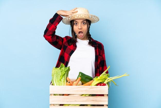 Jeune agriculteur femme tenant des légumes frais dans un panier en bois vient de réaliser quelque chose et a l'intention de la solution