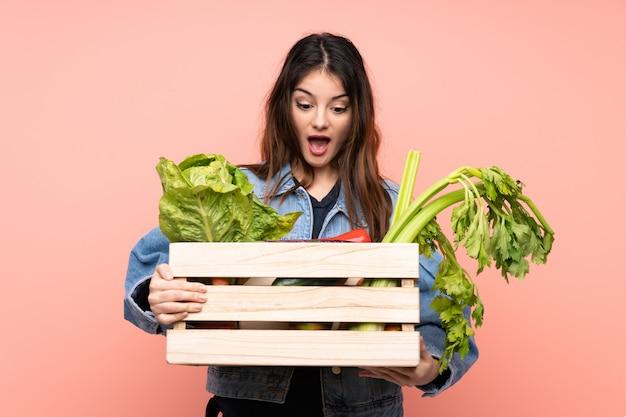 Jeune agriculteur femme tenant un panier plein de légumes frais