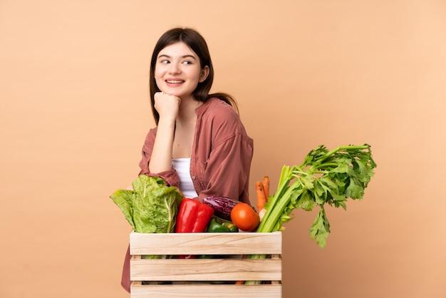 Jeune agriculteur fille avec des légumes fraîchement cueillis dans une boîte posant avec les bras à la hanche et souriant