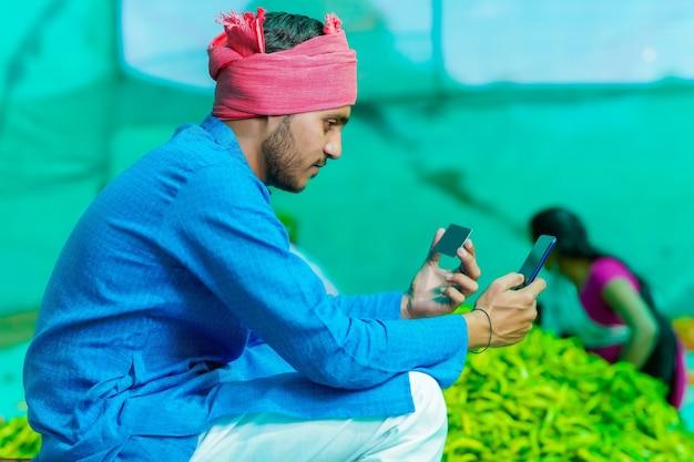 Jeune agriculteur indien à l'aide de smartphone et de carte au champ frisquet vert