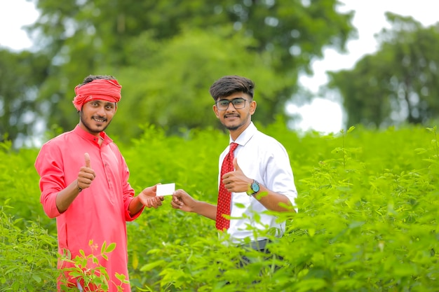 Jeune agriculteur indien avec un banquier sur le terrain