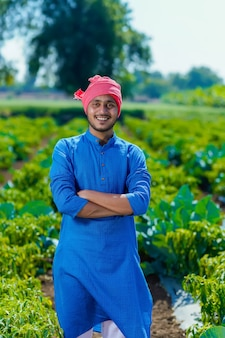 Jeune agriculteur indien debout au champ frisquet vert