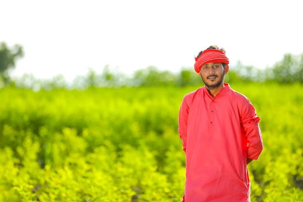 Jeune agriculteur indien debout dans le champ de pois pigeon vert