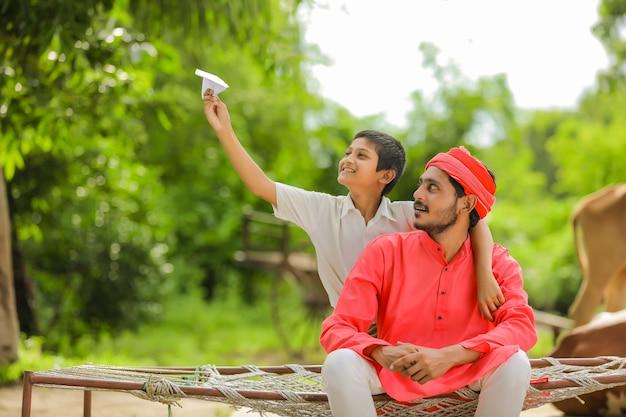 Jeune agriculteur indien jouant avec son fils