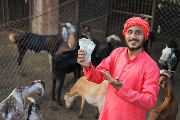 Jeune agriculteur indien montrant de l'argent à la ferme laitière de chèvre