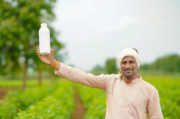 Jeune agriculteur indien montrant une bouteille d'engrais liquide sur le terrain de l'agriculture.
