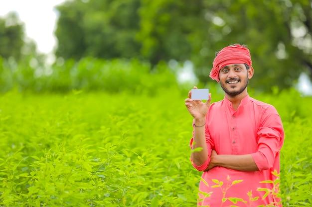 Jeune agriculteur indien montrant une carte de crédit
