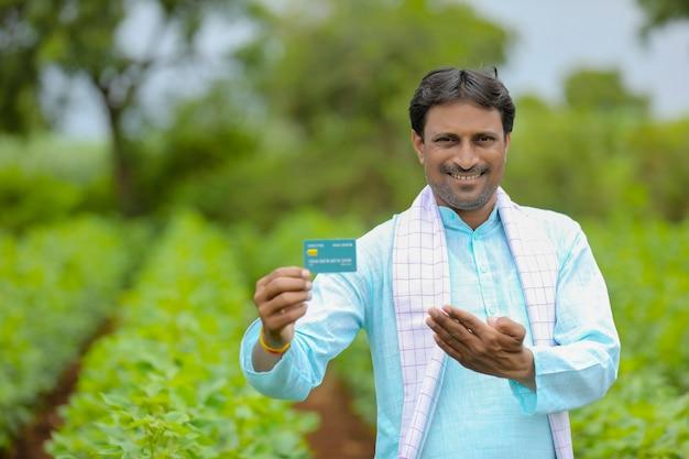 Jeune agriculteur indien montrant une carte de débit ou de crédit dans son champ d'agriculture verte