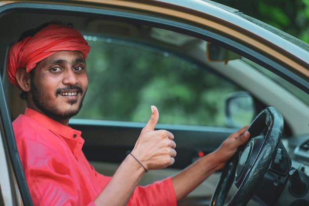 Jeune agriculteur indien montrant des coups dans la fenêtre de la voiture