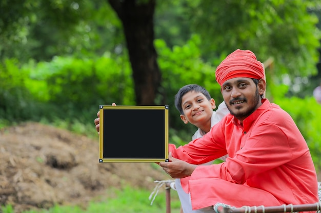Jeune agriculteur indien montrant un tableau blanc avec son enfant