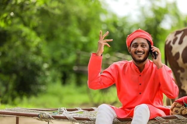 Jeune agriculteur indien parlant au téléphone