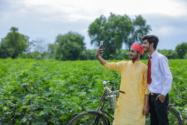 Jeune agriculteur indien prendre selfie avec agronome en smartphone