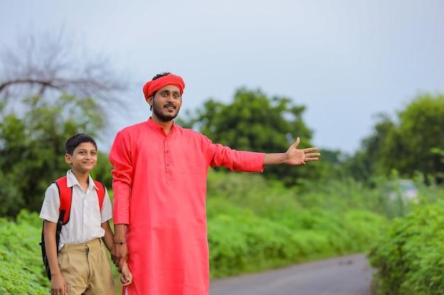 Jeune agriculteur indien avec son fils sur la route