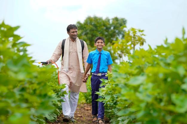 Jeune agriculteur indien avec son fils sur le terrain de l'agriculture verte.