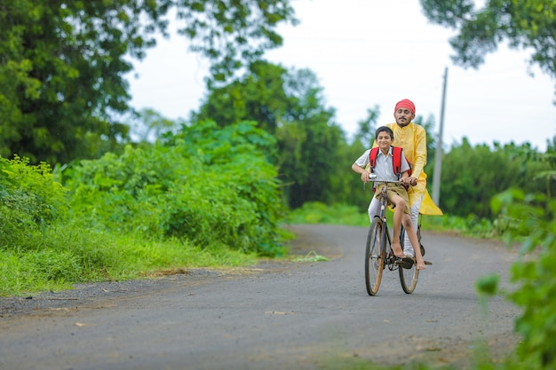 Jeune agriculteur indien et son fils vont à l'école sur cycle
