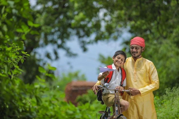 Jeune agriculteur indien et son fils vont à l'école