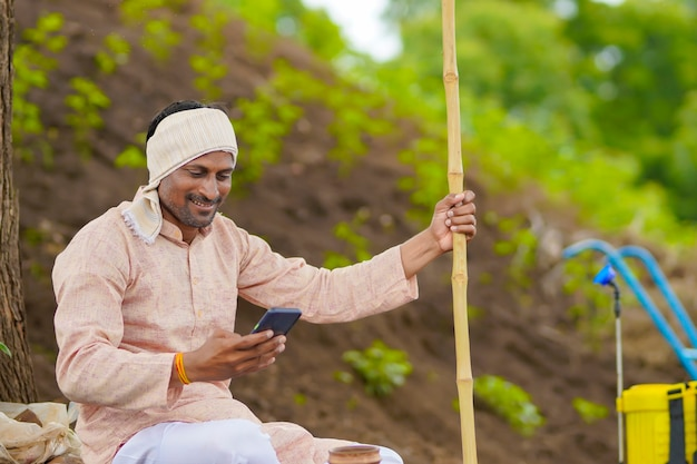 Jeune agriculteur indien utilisant un smartphone sur le terrain agricole.