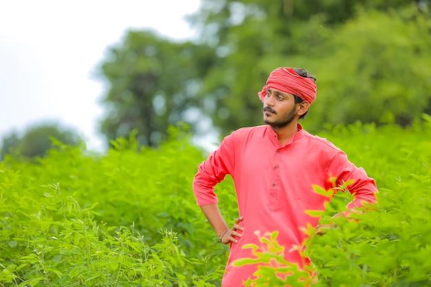 Jeune agriculteur indien en vêtements traditionnels sur le terrain