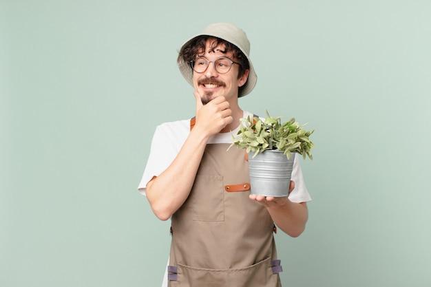 Jeune agriculteur souriant avec une expression heureuse et confiante avec la main sur le menton
