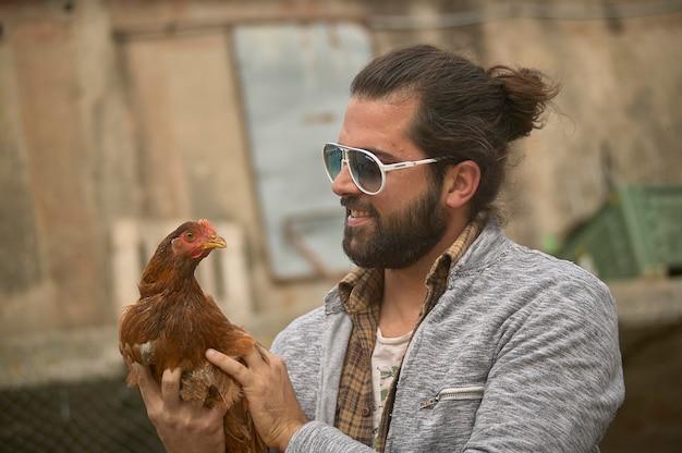 Le jeune agriculteur tient un poulet vivant dans sa main
