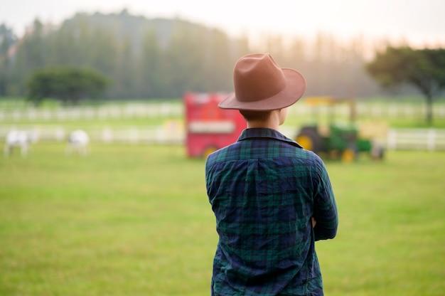 Un jeune agriculteur travaillant sur beau paysage de champ de pays à l'aube