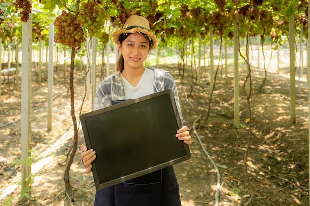 Jeune agricultrice asiatique tenant un tableau noir dans un vignoble de raisins, concept de fruits biologiques sains.