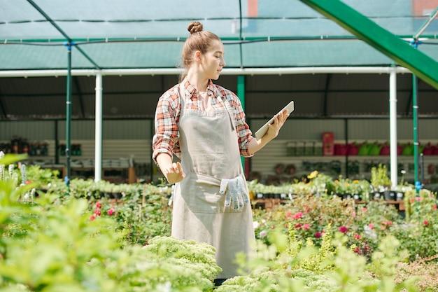 Jeune agricultrice blonde en vêtements de travail regardant la photo de la plante sur l'écran de la tablette et la comparant avec celle sur le parterre de fleurs