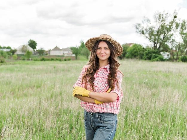 Jeune agricultrice dans le domaine. agriculteur de la famille dans un chapeau de paille, une chemise à carreaux et un jean dans le jardin