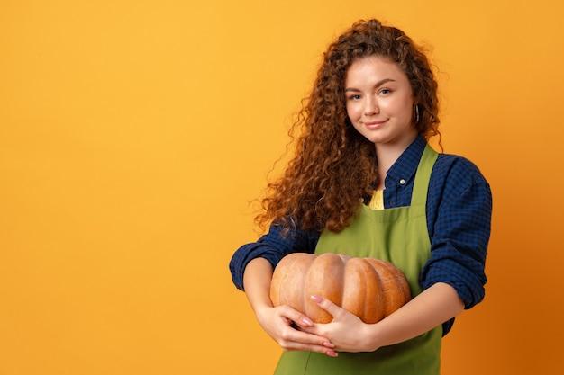 Jeune agricultrice souriante tenant une citrouille mûre sur fond jaune