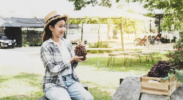 Jeune agricultrice tenant du raisin avec une caisse en bois après la récolte du vignoble frm concept de fruits sain