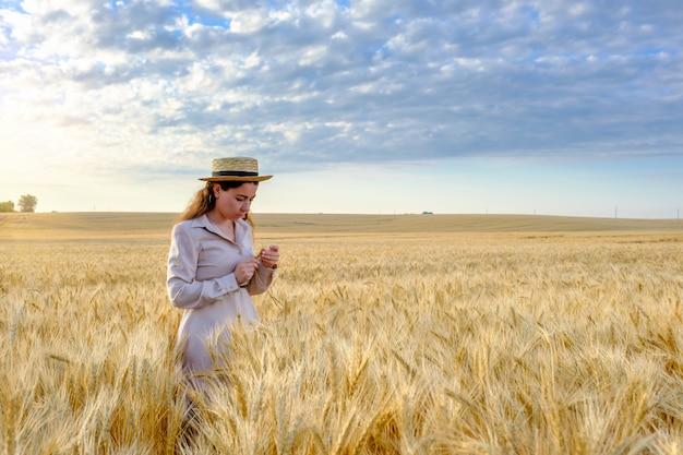 Jeune agronome aux cheveux longs dans un chapeau de paille détient une tige de blé dans un champ au lever du soleil. copier l'espace