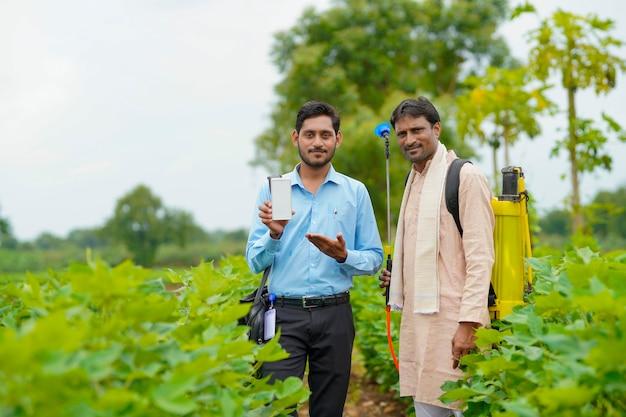 Jeune agronome ou banquier indien montrant un smartphone avec des agriculteurs dans un domaine agricole.
