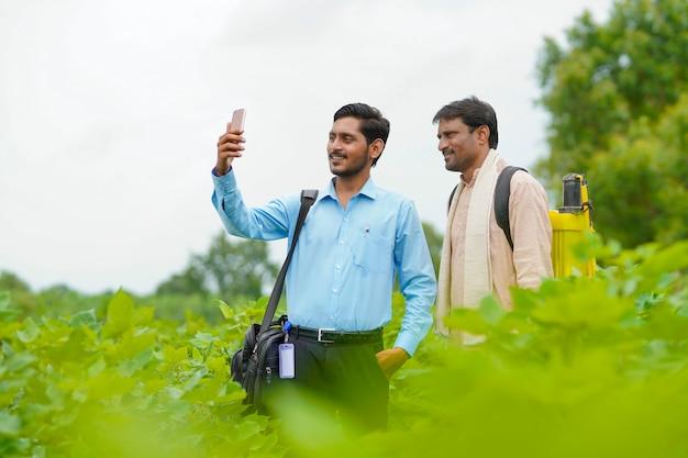 Jeune agronome ou banquier indien prenant un selfie avec un agriculteur dans un domaine agricole