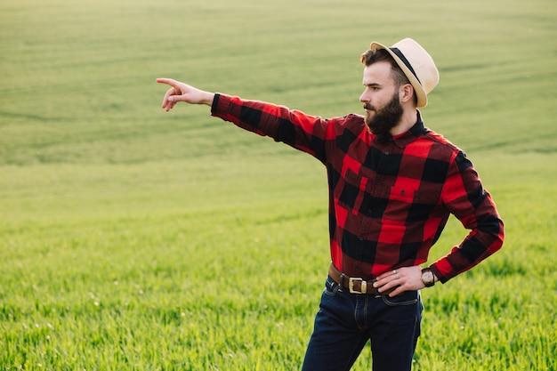 Jeune agronome barbu debout dans le champ de cultures de blé