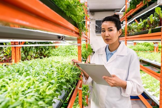 Jeune agronome contemporain d'origine asiatique tenant un document tout en faisant des recherches en serre
