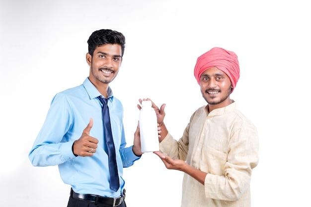 Jeune agronome indien donnant une bouteille à un agriculteur sur fond blanc.