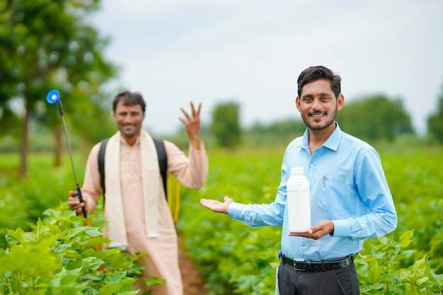 Jeune agronome indien donnant une bouteille d'engrais liquide à un agriculteur et disant des informations sur le produit sur le terrain de l'agriculture verte.