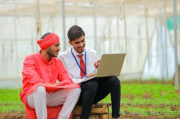 Jeune agronome indien montrant des informations à l'agriculteur dans un ordinateur portable à effet de serre