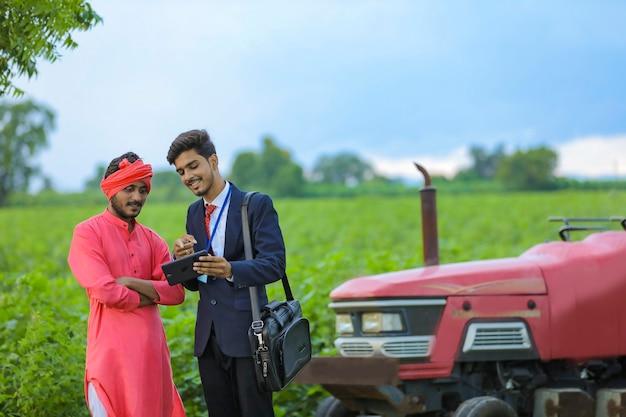 Jeune agronome indien montrant smartphone avec agriculteur