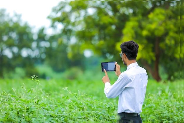 Jeune agronome indien avec smartphone au champ