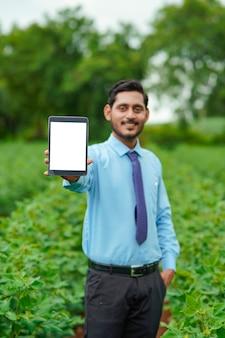 Jeune agronome ou officier indien montrant une tablette sur le terrain de l'agriculture.