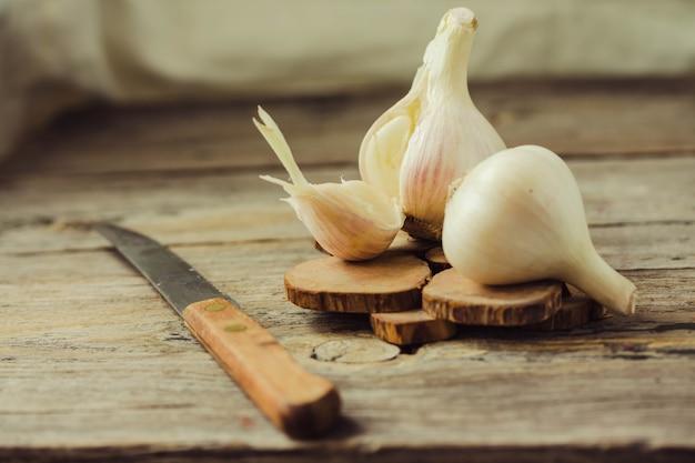 Jeune ail biologique frais sur une table en bois grise. mise au point sélective. légumes frais d'automne. pimenter. style rustique.