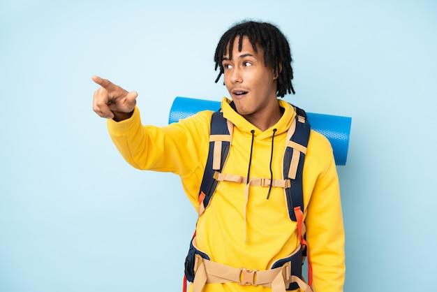 Jeune alpiniste afro-américain avec un gros sac à dos sur un mur bleu pointant loin