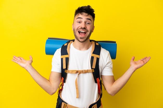 Jeune alpiniste caucasien avec un gros sac à dos isolé sur fond jaune avec une expression faciale choquée