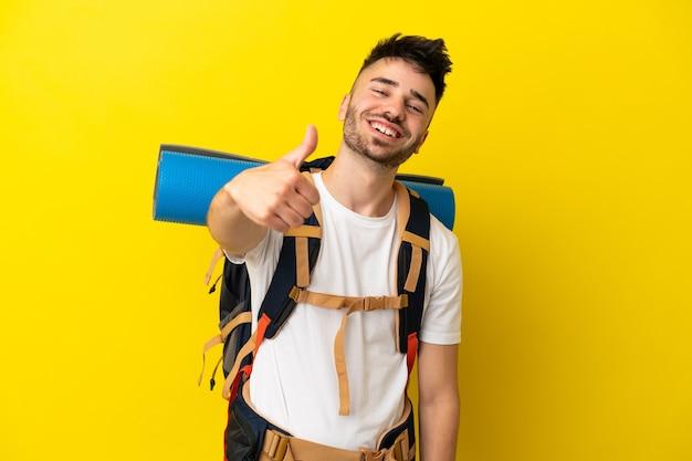 Jeune alpiniste caucasien avec un gros sac à dos isolé sur fond jaune avec le pouce levé parce que quelque chose de bien s'est produit