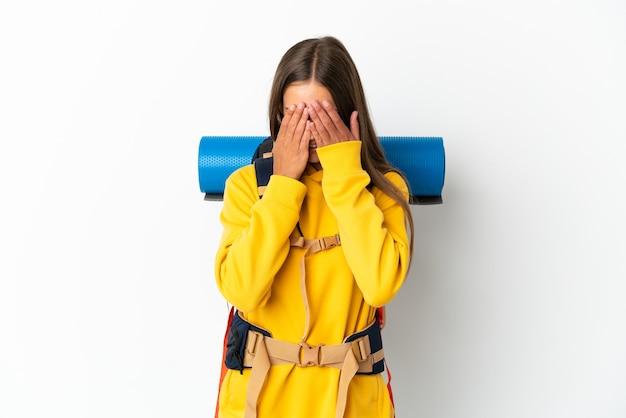 Jeune alpiniste femme avec un gros sac à dos sur fond blanc isolé avec une expression fatiguée et malade