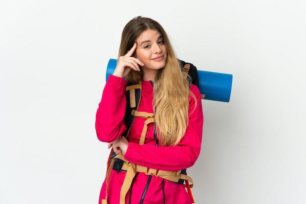 Jeune alpiniste femme avec un gros sac à dos fond isolé pensant une idée